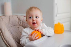 Dziecko samodzielnie siedzi w krzesełku do karmienia dla dzieci