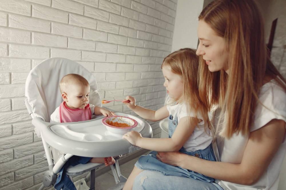 Mama i córka karmią dziecko na krzesełku do karmienia niemowlat