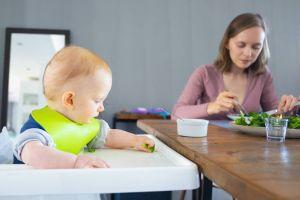 Rodzice jedzą swobodnie obiad kiedy dziecko siedzi w wygodnym krzesełku do karmienia